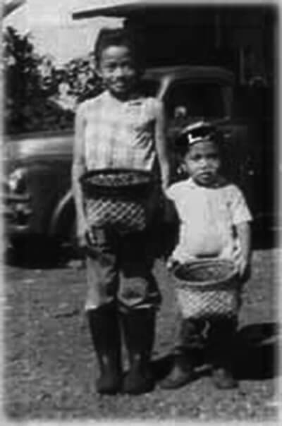 Children with child-sized versions of baskets used for picking coffee, ca. 1960s. (Photo courtesy Isabelo Sebastian.)