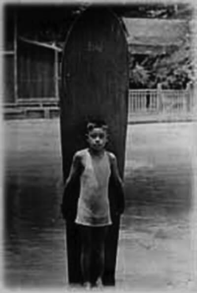 Interviewee Minoru Aoki stands in Hamohamo Stream (no longer in existence) with surfboard, Waikiki, ca. 1920s. (Photo courtesy Minoru Aoki.)