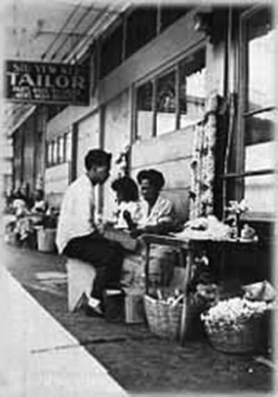 Interviewee Sophia Ventura with nephew at her Kekaulike Street lei stand in downtown Honolulu, ca. 1940. (Photo courtesy Charlotte Fuller.)